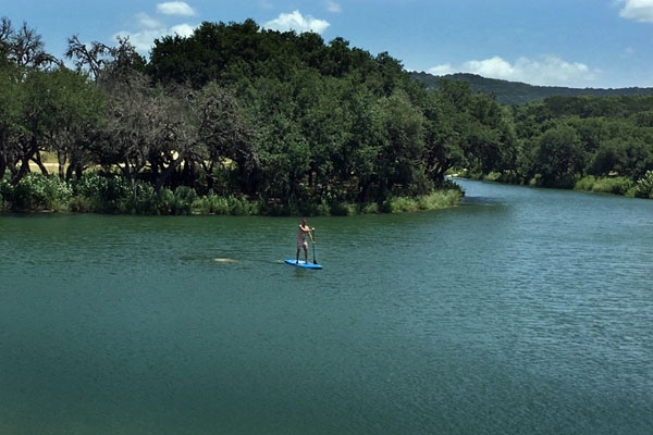 Paddleboarding on Pipe Creek, a ranch actiivty